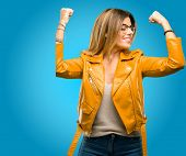 Beautiful young woman showing biceps expressing strength and gym concept, healthy life its good, blu poster