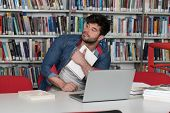 Confused Male Student Reading Many Books For Exam poster