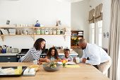 Young black family busy together in their kitchen poster