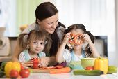 Happy Family Mom And Kids Preparing Vegetables Together At Home In The Kitchen poster