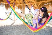 Happy Stylish Family With Cute Daughter Relaxing In Hammock On Summer Vacation In Evening Sun Light  poster
