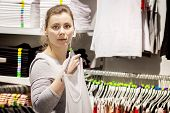 Young White Woman In Stylish Clothes Shop. The Girl Chooses Clothes In Fashionable Boutique. Shoppin poster