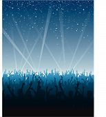 stock photo of pop star  - Fans raise their hands at a concert under a night sky with searchlights in the background - JPG