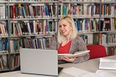 Happy Female Student Reading From Book In Library poster