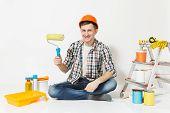 Man In Orange Protective Helmet Sitting On Floor Using Paint Roller. Instruments For Renovation Apar poster