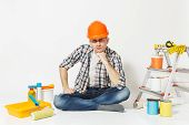 Serious Man In Orange Protective Helmet Sitting On Floor With Instruments For Renovation Apartment R poster