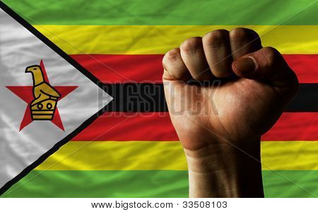 Hard Fist In Front Of Zimbabwe Flag Symbolizing Power