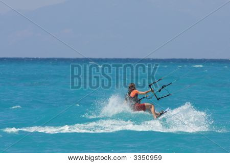 Kite Boarder Riding The Waves  On A Sunny Day