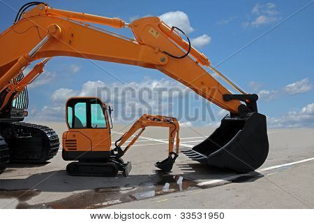 Two Excavators On A Concrete Platform
