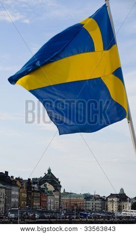 Swedish Flag Waving Over The Buildings Of Stockholm Old Town