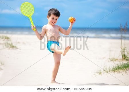 Happy little boy playing on tropical beach