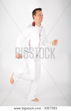 Man In White Sports Suit Runs Barefoot