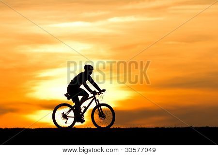 silhouette of a cyclist in sunset