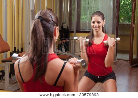 Beautiful smiling young girl exercising in the gym with dumbbells