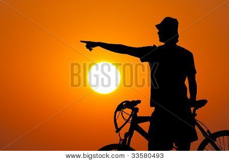 Silhouette of the bicycle rider against sun and orange sky showing something in the distance