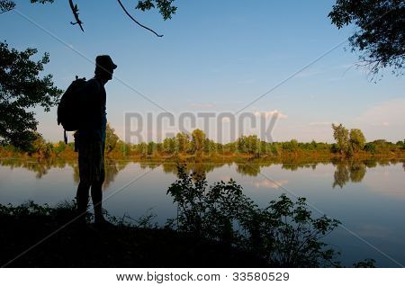 Silhouette of the man standing on the river shore