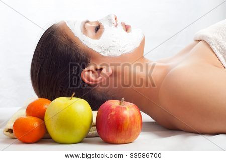 Beautiful young woman lying on massage table with natural facial mask on her face