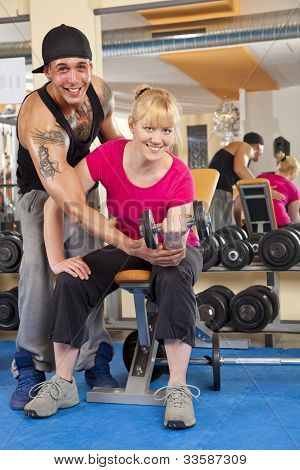 smiling woman exercising in gym with trainer