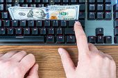 Money On The Keyboard As The Concept Of Earning Online. Male Hand Presses Enter Key poster