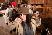 stock photo of chug  - Cowgirl with bottle sipping whiskey from a shot glass - JPG