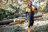 Full Length Portrait Of A Professional Lumberman In Protective Workwear With A Chainsaw And Wooden L poster