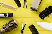 Hairdresser Tools On Yellow Wooden Background. Frame With Hairdresser Equipment. Space For Text. poster