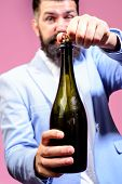 Celebration, Drink, Alcohol And Holidays Concept. Bearded Man Opens Bottle. Sommelier With Wine Bott poster