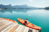 Little Boy Sitting On Orange Kayak Near The Pier And Dangling Feet Making Radial Waves On Cheow Lan  poster