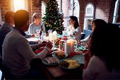 Family and friends dining at home celebrating christmas eve with traditional food and decoration, ce poster