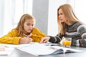 Cute upset little girl doing homework with her mom while sitting at the table at the living room poster