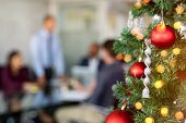 Close up of decorated christmas tree in office with business people working in background. Xmas cele poster