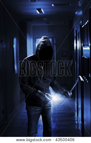 Burglar with flashlight and crow bar in a dark office building.