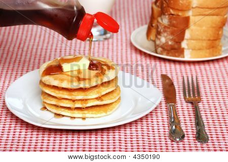 Maple Syrup Being Poured On A Stack Of Pancakes