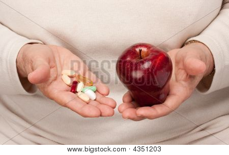 Senior Woman Holding Pills And Apple