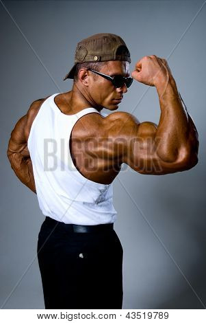 A Strong Man In Sunglasses Shows His Muscles.