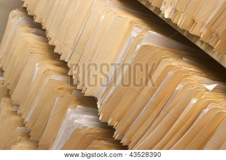Rows Of File Folders Arranged On Shelf With Client Data