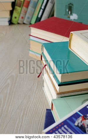 A Variety Of Books In Stacks On The Table