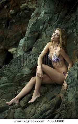 Swimsuit model posing sexy in front of black lava field on at Palos Verdes CA