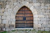 foto of fortified wall  - Old medieval castle gate in a fortified granite wall - JPG