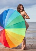 stock photo of nudist beach  - Young naked girl with a colorful umbrella on the beach - JPG