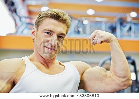 Humeral portrait of smiling bodybuilder who demonstrates tensed biceps