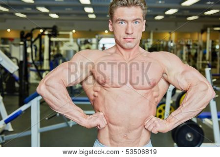 Bodybuilder poses with his arms akimbo in gym hall