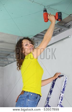 Woman with an electric screwdriver to fasten drywall on ceiling