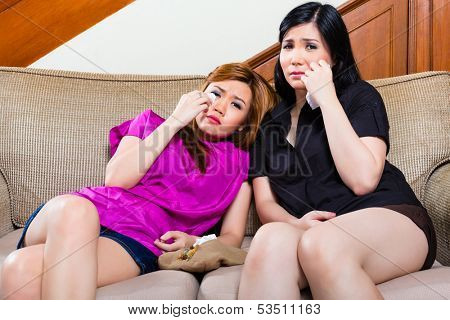 Two Indonesian girl friends sitting on the couch crying, perhaps they have heartache or watch a sad movie on TV