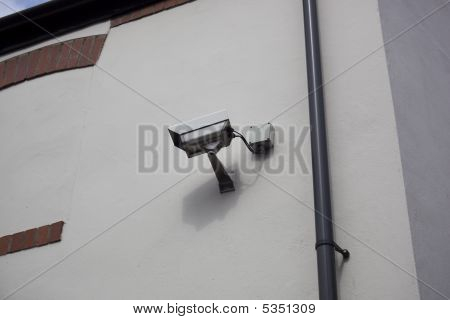 Security Camera Mounted On White Wall
