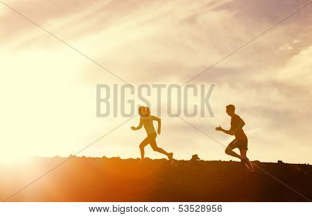 Silhouette of Man and woman running together into sunset, Wellness fitness concept