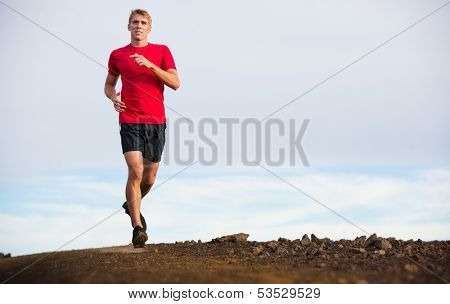 Athletic man jogging outside, training outdoors. Running on trail at sunset