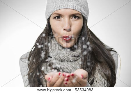 Attractive Woman Blowing Snowflakes