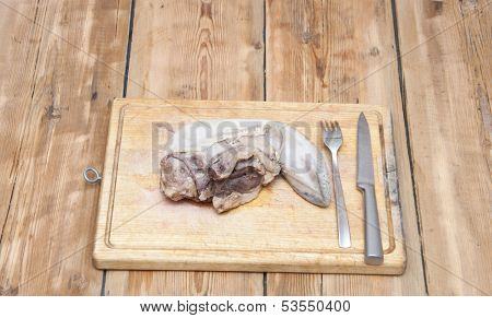 Tongue. Raw meat food on wooden board