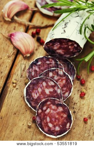 Close-up traditional sliced meat sausage salami on wooden board with head of garlic and green herbs